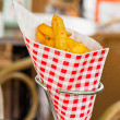 Stock Photo: French fries in red and white blocked paper bag on table outdoor