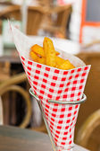 French fries in red and white blocked paper bag on table outdoor — Stock Photo