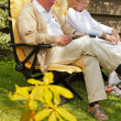Senior couple sitting in garden reading a book. Summer time. — Foto de Stock