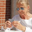 Stock Photo: Senior woman playing card game outdoor in garden.