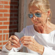 Senior woman playing card game outdoor in garden. — Stock Photo