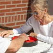 Senior couple playing dice game outdoor in garden. Yahtzee. — Стоковая фотография