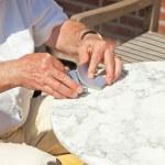 Senior man shaking cards game outdoor in garden. — Stock Photo