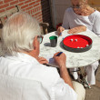 Senior couple playing dice game outdoor in garden. Yahtzee. — Stock Photo