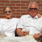 Happy senior couple sitting outdoors in garden enjoying fruit ju — Stock Photo