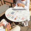 Stock Photo: Senior couple playing card game outdoor in garden. Top view.