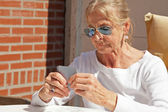 Senior woman playing card game outdoor in garden. — Стоковое фото