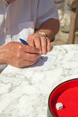 Senior man writing his score on paper outdoor in garden. Playing — Stock Photo