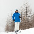 Happy ski woman standing in snow with pine trees. — Stock Photo #26059745