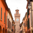 Stock Photo: Street with houses and tower with clock in Castel San Pietro. Em