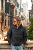 Young man with long blonde hair and sunglasses on bridge in Veni — Stock Photo