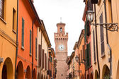 Street with houses and tower with clock in Castel San Pietro. Em — Foto de Stock