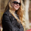 Stock Photo: Smiling young blonde girl with sunglasses and braces in park.