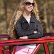 Smiling young blonde girl with sunglasses and braces in park. — Stock Photo