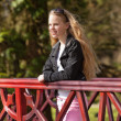 Young girl with long blonde hair and sunglasses on bridge in par — Stock Photo #26713091