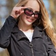 Smiling young blonde girl with sunglasses and braces in park. — Stock Photo #26713093