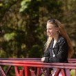 Stock Photo: Young girl with long blonde hair and sunglasses on bridge in par
