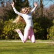 Blonde girl jumping on field of grass in park. — Stock Photo