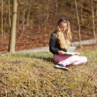 Blonde girl sitting in grass reading a book. Outdoor park. — Stockfoto