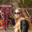 Young girl with long blonde hair and sunglasses on bridge in par — Stock Photo #26713213