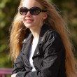 Young girl with long blonde hair and sunglasses on bridge in par — Stock Photo