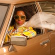Vintage 70s fashion afro woman with sunglasses driving in brown — Stock Photo