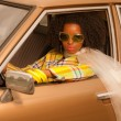 Royalty-Free Stock Photo: Vintage 70s fashion afro woman with sunglasses driving in brown
