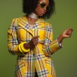 Dancing retro 70s fashion african woman with sunglasses. Yellow — Lizenzfreies Foto