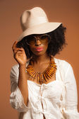 Retro 70s fashion afro woman with sunglasses and white hat. Brow — Stock Photo