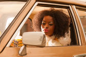 Retro 70s fashion african american woman driving in gold seventi — Stock Photo