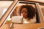 Retro 70s fashion african american woman driving in gold seventi — Stock Photo