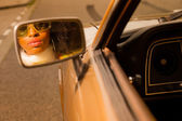 Retro 70s afro fashion woman with sunglasses looking in mirror o — Stock Photo