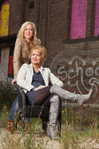 Blonde mother and daughter portrait in urban scenery. — Stock Photo