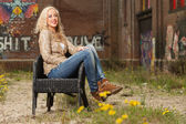 Pretty blonde fashion girl sitting in chair outdoor in urban env — Stock Photo