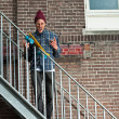 Cool skateboarder with woolen hat standing on iron stairway. His — Stock Photo #27392803