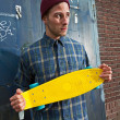 Urban fashion skateboarder with woolen hat holding his skateboar — Foto Stock