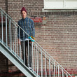 Cool skateboarder with woolen hat standing on iron stairway. His — Stock Photo #27394075