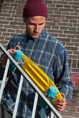 Cool hip skateboarder with woolen hat checking the rail of iron — Stock Photo