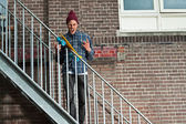 Cool skateboarder with woolen hat standing on iron stairway. His — Stock Photo
