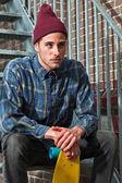 Urban skateboarder with woolen hat holding his skateboard sittin — Stock Photo