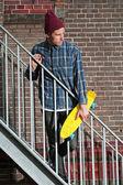 与羊毛帽子举行他的滑板站酷滑板手 — 图库照片