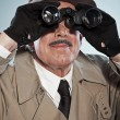 Vintage detective with mustache and hat. Looking through binocul — Stock Photo #27481745