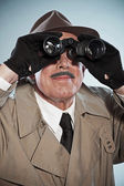 Vintage detective with mustache and hat. Looking through binocul — Stock Photo
