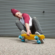 Street skateboarder with woolen cap doing trick on street in fro — Stock Photo