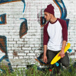Hip cool urban fashion skateboarder with woolen hat posing in fr — Stockfoto
