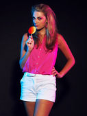 Retro 80s fashion disco girl with blonde hair and lollipop. Blac — Stock Photo