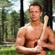 Shirtless muscled fitness lumberjack man with axe in forest. — Stock Photo