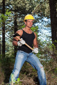 Muscled lumberjack with black shirt and axe in forest. Wearing y — Stock Photo