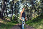 Muscled man with black shirt and axe in forest. — Stock Photo