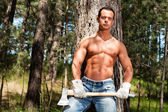 Shirtless handsome muscled lumberjack man with axe in forest. — Stock Photo
